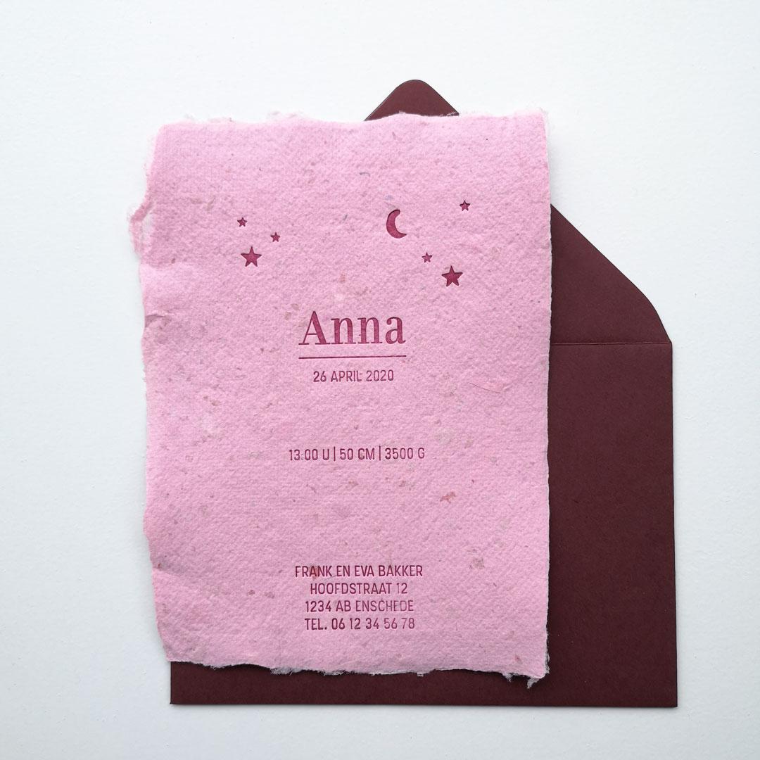 Geboortekaartje op roze handgeschept papier en een donkerrode envelop. De tekst is gedrukt in donkerrood en de kaart is versierd met sterren en een maantje.