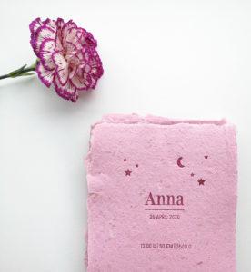 Geboortekaartje op roze, handgeschept papier met donkerrode tekst en een versiering met sterren en een maantje.