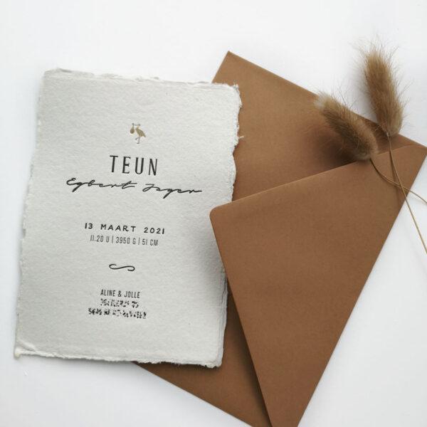 Geboortekaartje Teun op handgeschept papier. Bovenaan een goudkleugie ooievaartje.