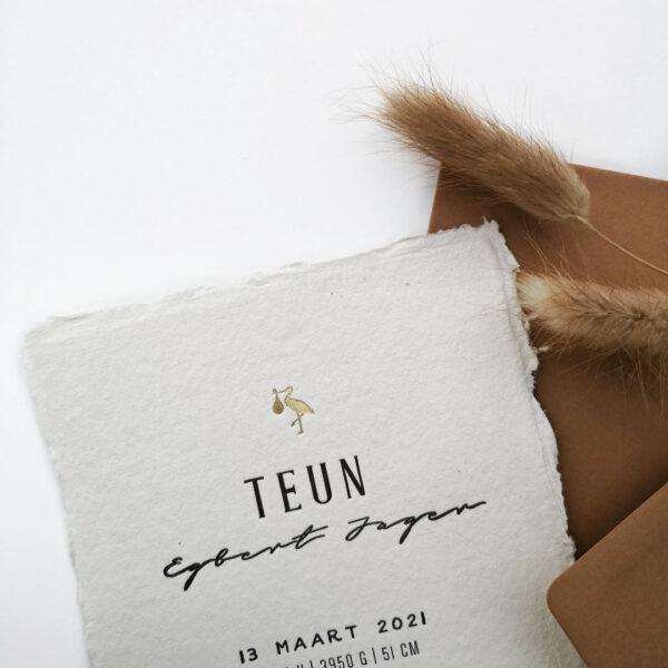 Detail foto van het geboortekaartje van Teun. Handgeschept papier met zwart letters en bovenaan een ooievaartje in goudfolie.
