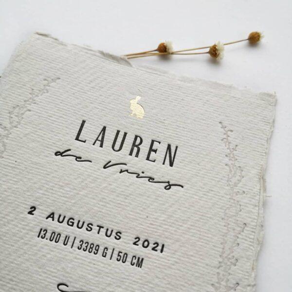 Detail van een geboortekaartje op handgeschept papier met een haasje in goudfolie