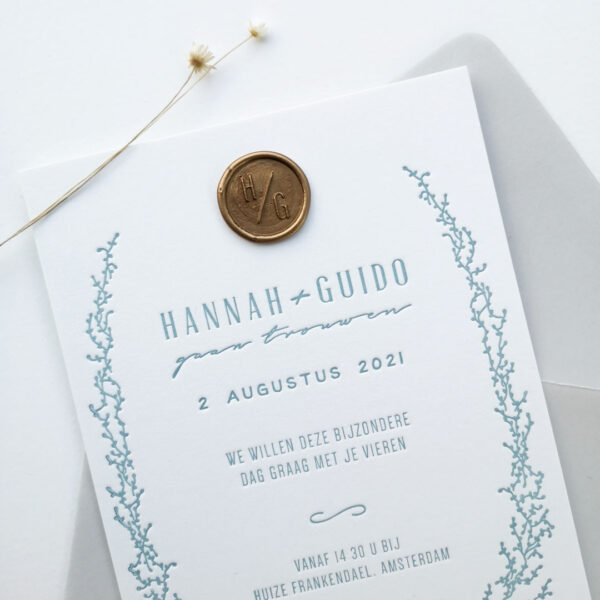 Close up van een trouwkaart met lichtblauwe opdruk en een goudkleurige waxzegel met initialen