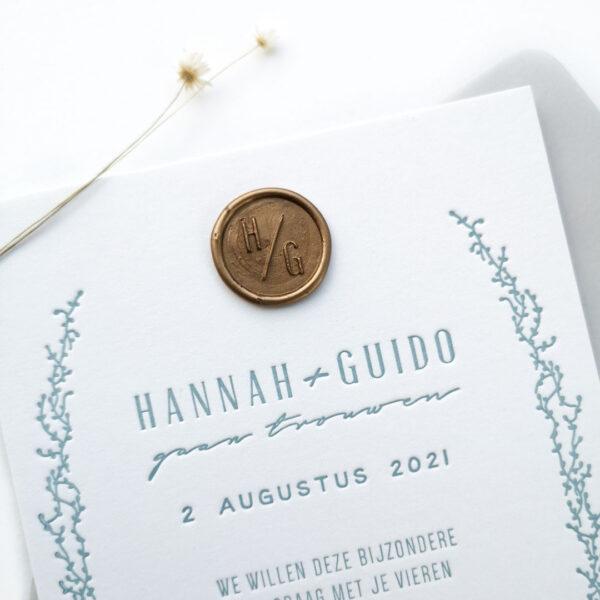 Detail foto van een trouwkaart met lichtblauwe opdruk en een goudkleurige waxzegel