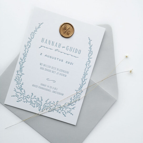 Trouwkaart met lichtblauwe opdruk en een goudkleurige waxzegel met initialen en een grijze envelop