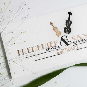Close up van de trouwkaart van Frederiek en Sander. Met een viool en een cello gedrukt in goud en zwart.