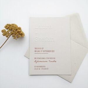 Trouwkaart met beide namen gepreegd. De overige tekst gedrukt in een terracotta kleur. Een gele droogbloem aan de linkerkant van de foto.