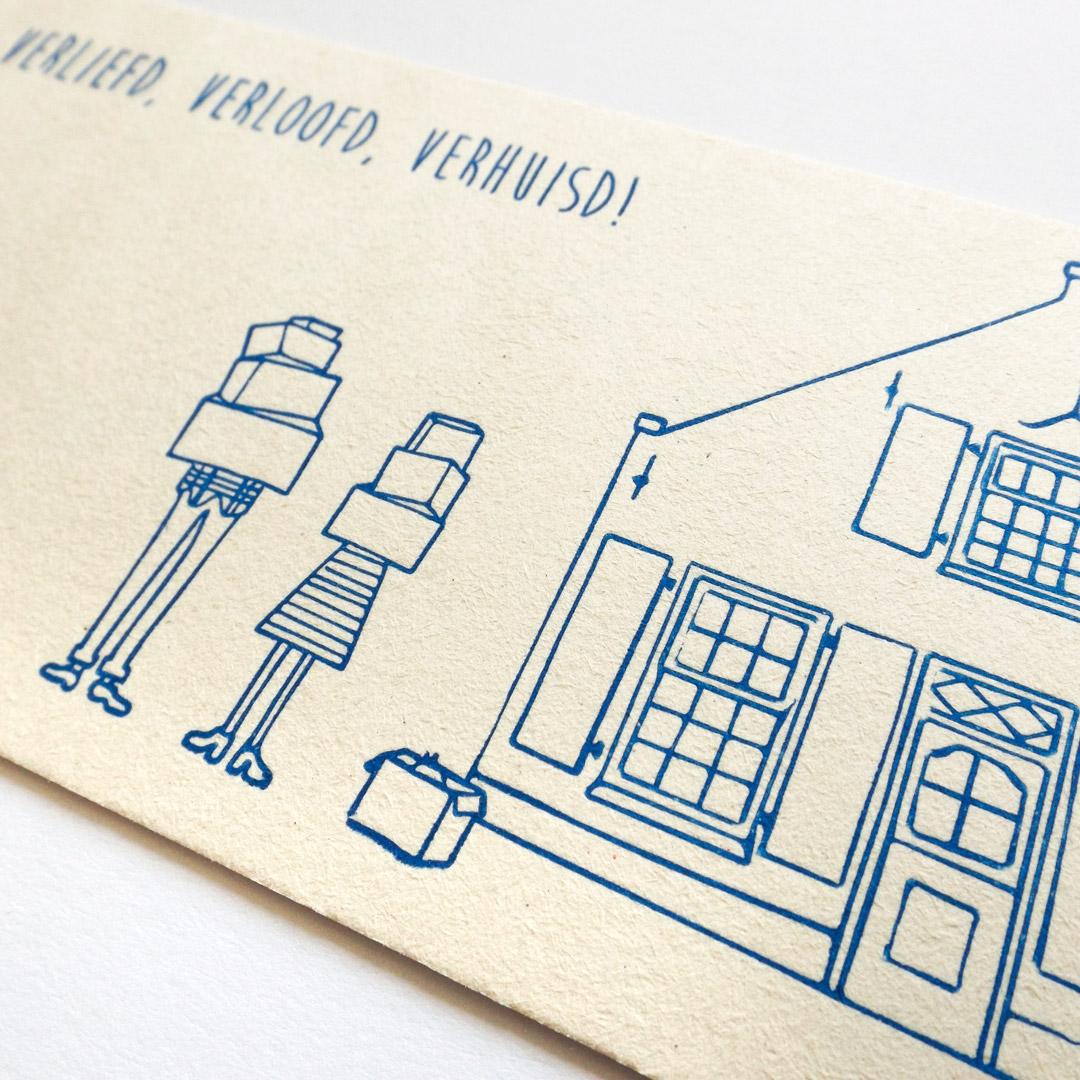 Close up van een verhuiskaart met de tekst verliefd, verloofd, verhuisd en een tekening van de bewoners en hun nieuwe huis.